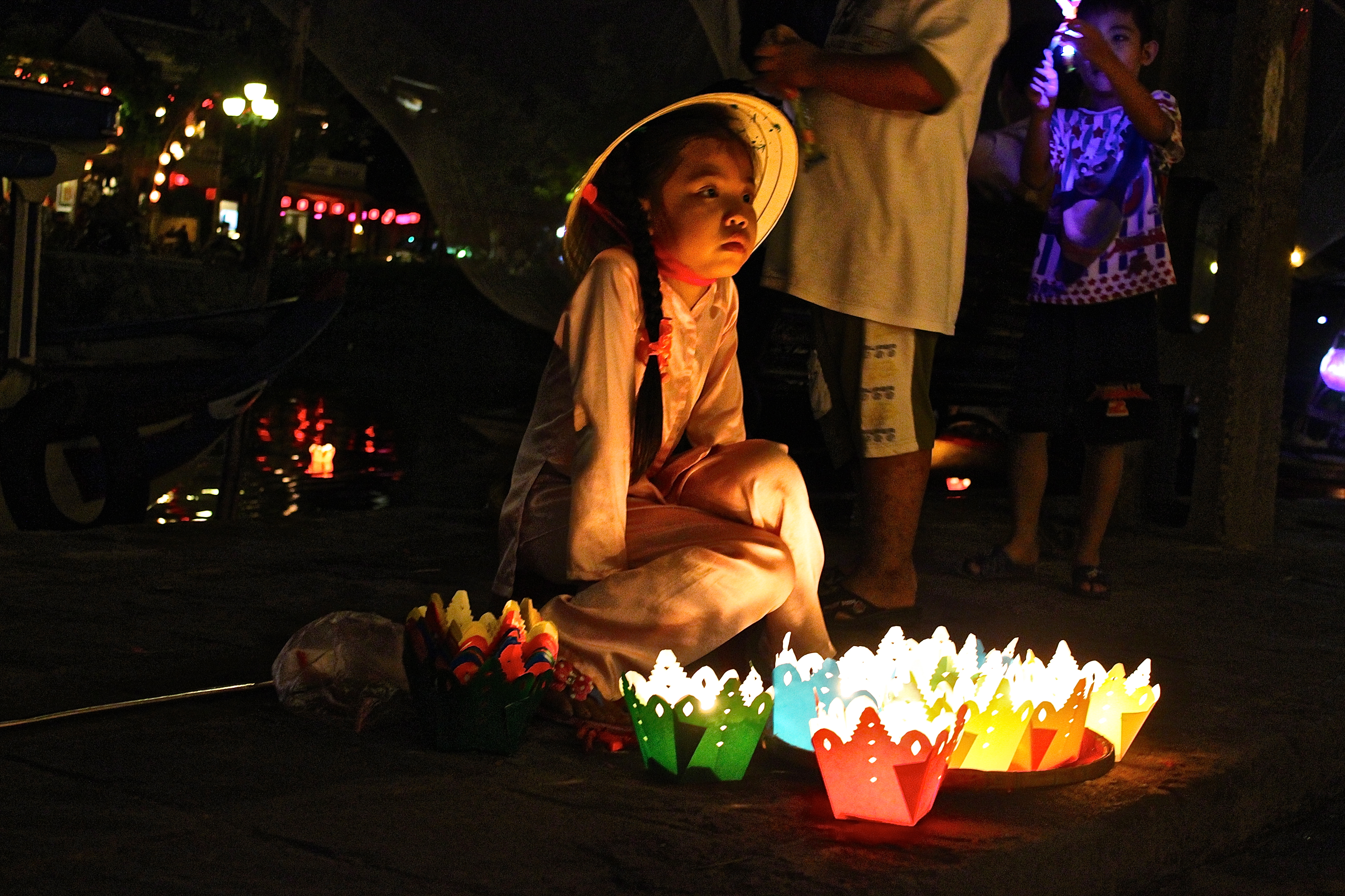 A young girl peddles candles by the riverside in the UNESCO World Heritage town of Hoi An © Isheeta Sumra